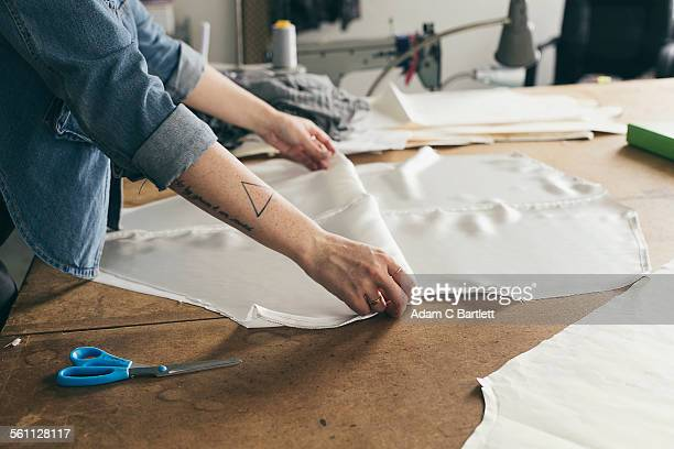Young female seamstress folding pattern component in fashion studio