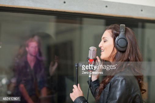 Young female singer in recording studio