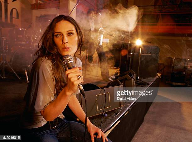 Young Female Singer Performs With a Band on a Smokey Stage