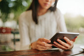 Shot of young female sitting at cafe table. Woman using tablet at coffee shop. Focus on digital tablet.