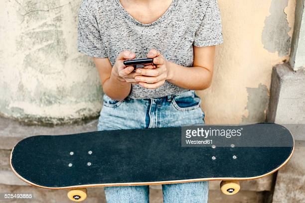 Young female skate boarder with smartphone and skateboard in front of a facade, partial view