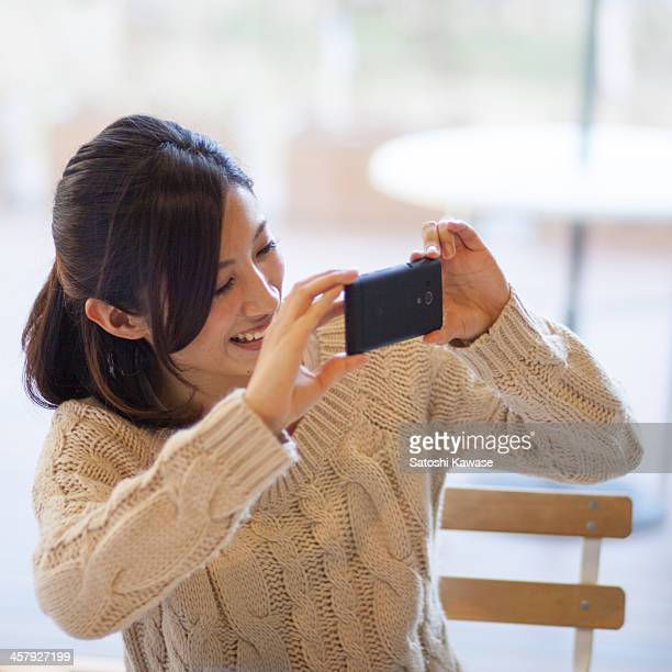 Young female smiley taking pictures with a smart p