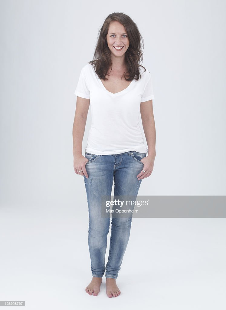 young female smiling with hands in pockets : Stock Photo