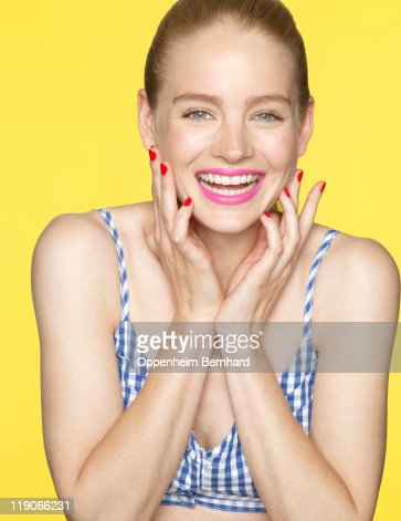 young female smiling with hands to her face