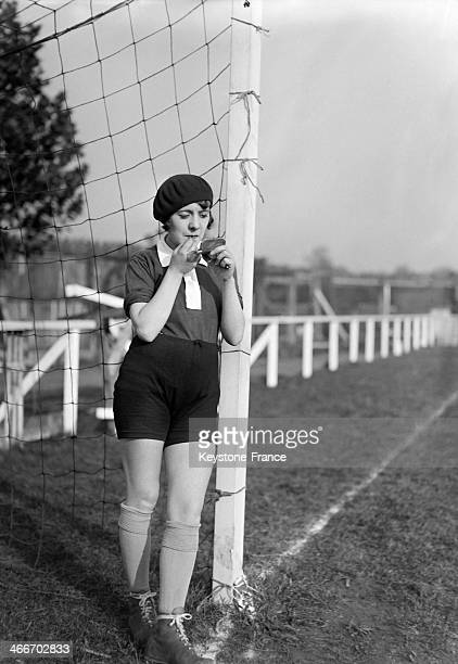 A young female soccer player is checking herself in a pocket mirror before a match in 1929 in France