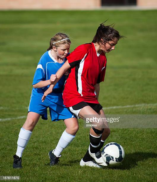 Young Female Soccer Player Sheilds Ball from Defender