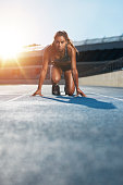 Vertical shot of young female sprinter taking ready to start position facing the camera.  Woman athlete in starting blocks with sun flare.