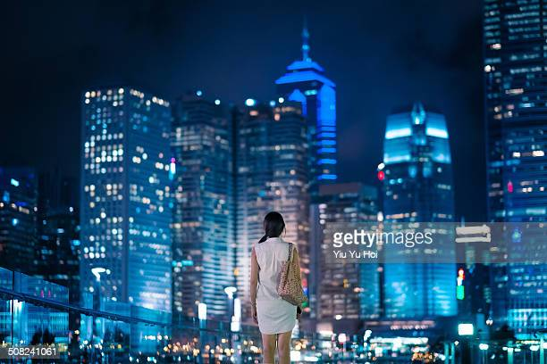 Young female standing in front of modern city