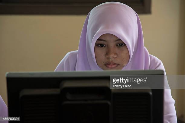 A young female student in the computer room in a 'pondok' a school providing general and religious studies
