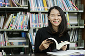 Young female student reading book in library.