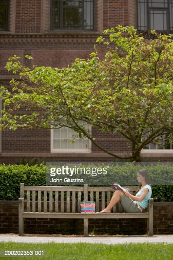 young female student reading on bench side view stock foto getty images. Black Bedroom Furniture Sets. Home Design Ideas