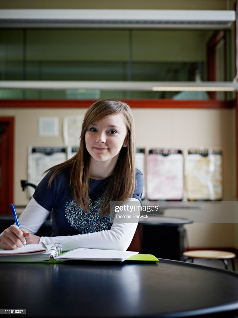 Young female student sitting in classroom working : Stock Photo