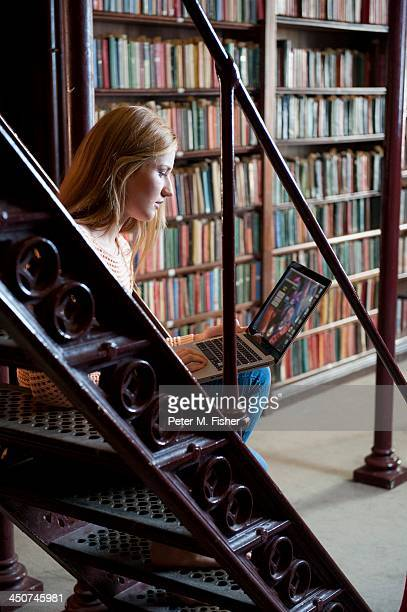 Young female student sitting on lattice staircase in an old library using a laptop computer