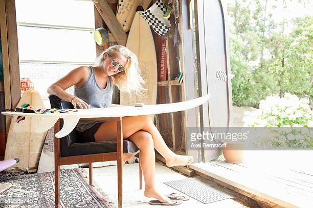 Young female surfer sitting in shed waxing her surfboard