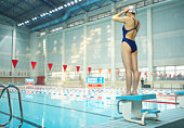 Young female swimmer adjusting swimming cap atop starting block