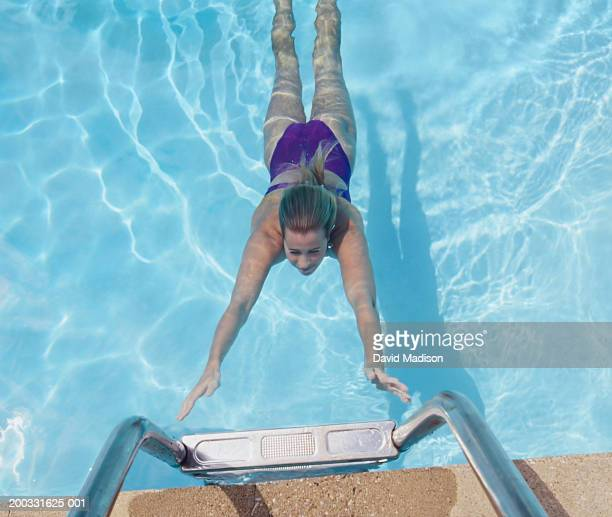 Young female swimming underwater, reaching for ladder, overhead view