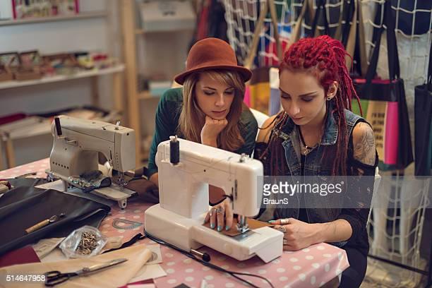 Jovem mulher a trabalhar num desenhar e máquinas de costura em Estúdio de projeto.
