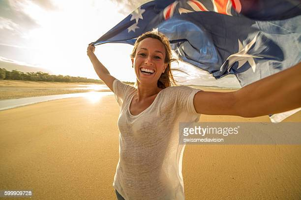Young female takes selfie portrait on beach with flag