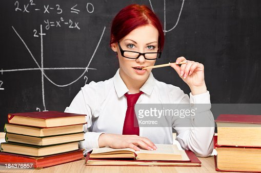 Young female teacher at desk biting pen provocatively