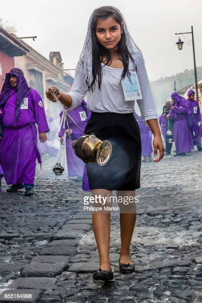 Young female teen burning incense during Holy Week in Antigua, Guatemala