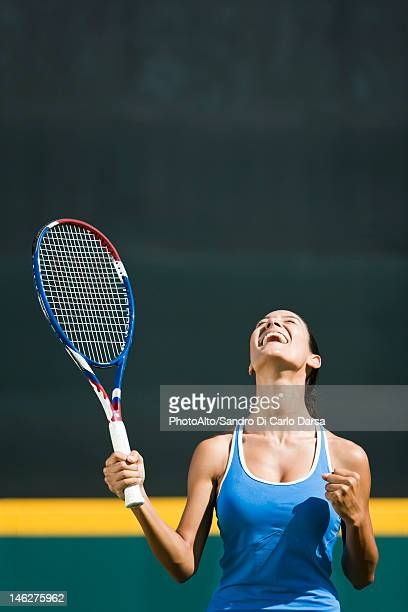 Young female tennis player cheering, portrait