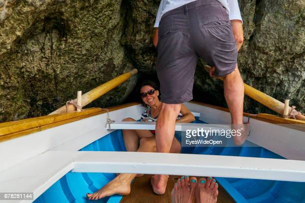 A young female Tourist is ducking down in a rowing boat to pass the small Entrance of the Blue Grotto at the Island of Capri on June 24 2015 in...