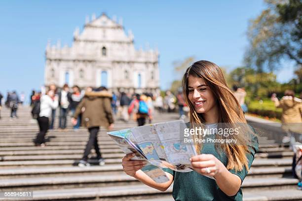 Young female tourist reading map in front of St Pauls Cathedral ruins, Macau, Hong Kong, China