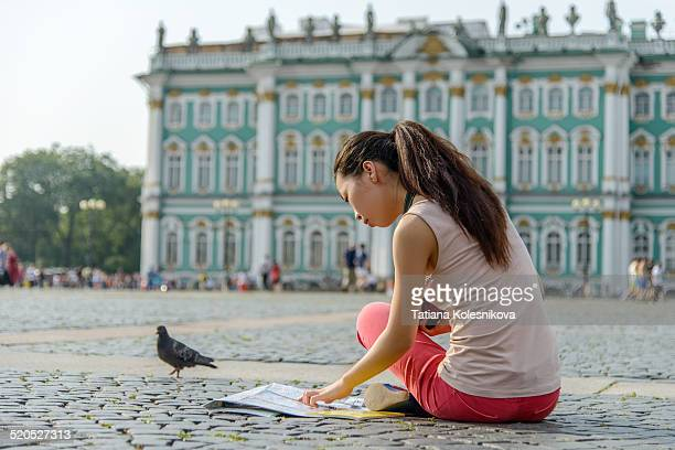 Young female tourist studying map