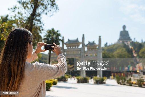 Young female tourist taking smartphone photographs of Tian Tan Buddha, Po Lin Monastery, Lantau Island, Hong Kong, China