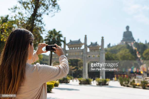 Young female tourist taking smartphone photographs of Tian Tan Buddha, Po Lin Monastery, Lantau Island, Hong Kong, China