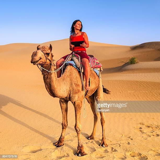 Junge weibliche Touristen mit tablet PC auf einem Kamel