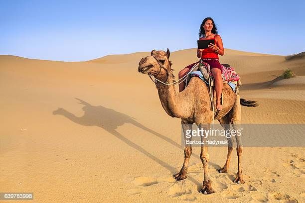 Young female tourist using digital tablet on camel, Rajasthan, India