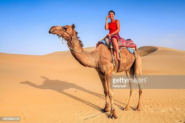 Femme jeune touriste à l'aide de téléphone portable sur un chameau, Rajasthan, Inde