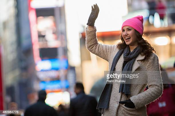 Young female tourist waving from street, New York City, USA