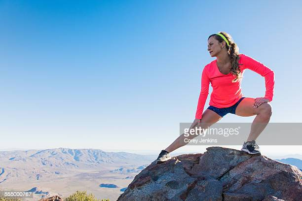 Young female trail runner stretching on rock on Pacific Crest Trail, Pine Valley, California, USA