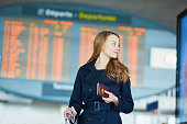 Young woman in international airport near the flight information board, holding French passport in her hand and using her mobile phone