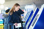 Young woman in international airport doing self check-in, stressed and concerned. Missed, delayed or canceled flight concept
