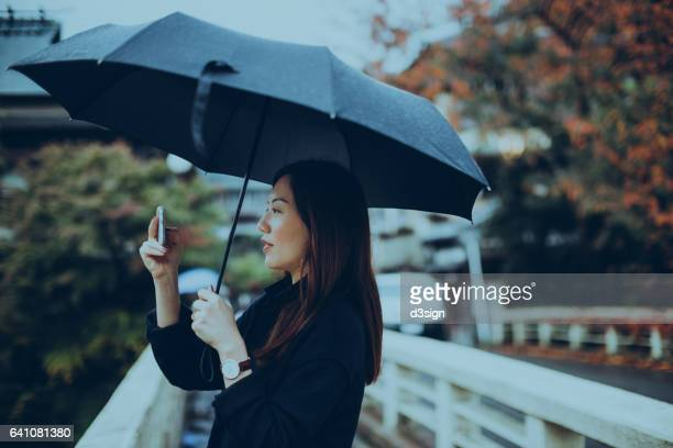 Young female traveller holding umbrella and taking pictures with smartphone on street