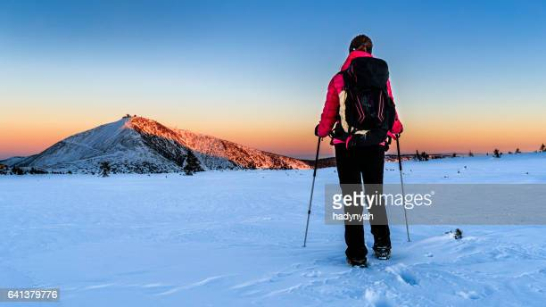 Young female trekker watching sunset in the mountains