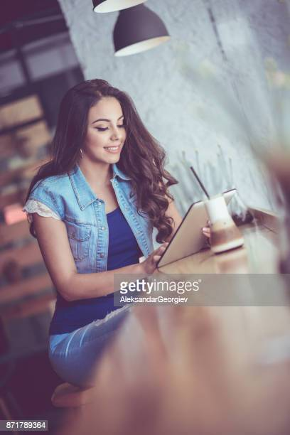 Young Female Using Digital Tablet at her Favorite Coffee Shop