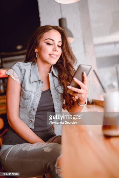 Young Female Using Smartphone at her Favorite Coffee Shop