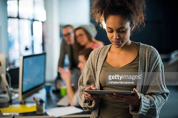Young female using tablet with colleagues