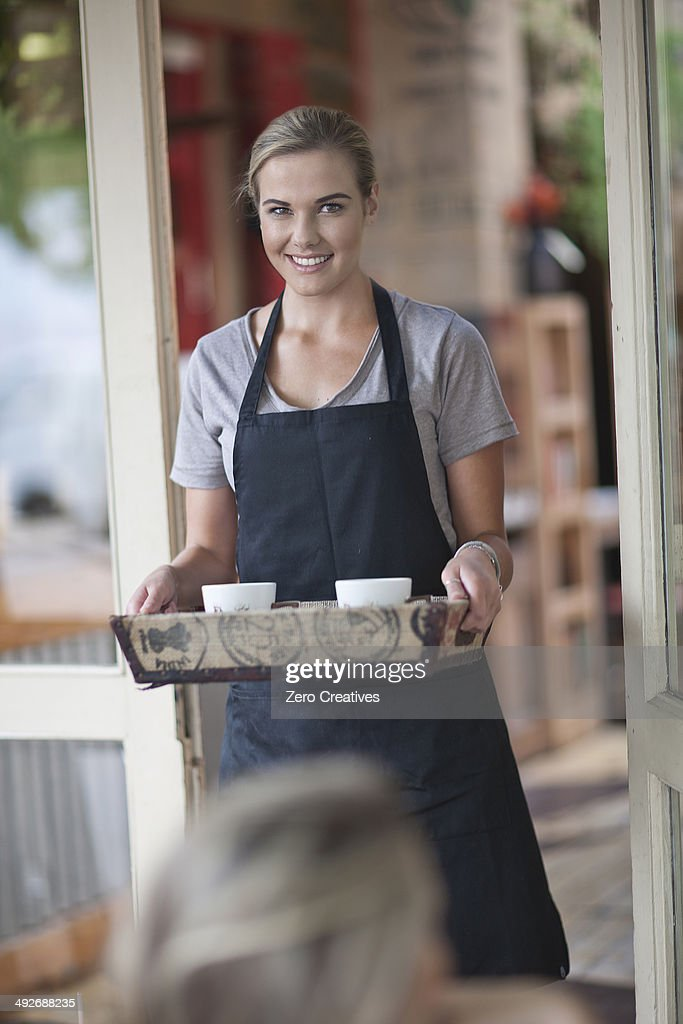 Young female waitress carrying tray of coffee cups in cafe
