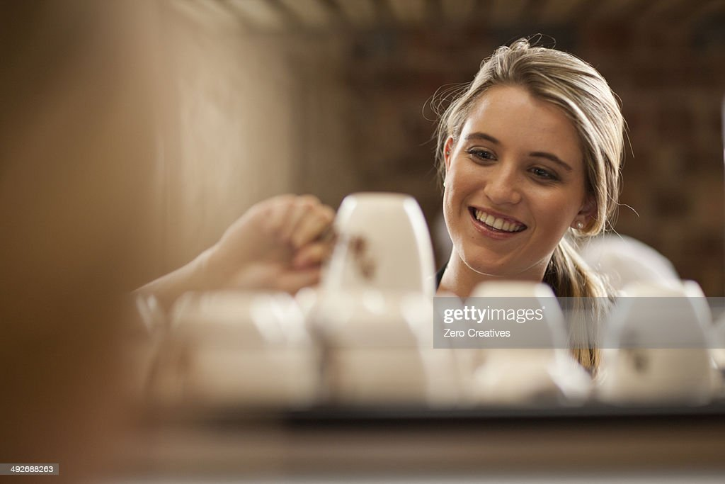Young female waitress picking up cup from tray in cafe