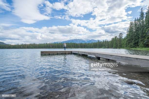 Young female walking on lake pier
