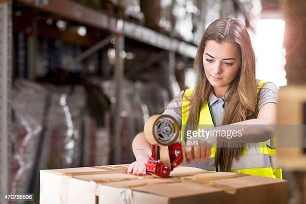 Jovem fêmea Trabalhador de armazém caixas de embalagem para envio