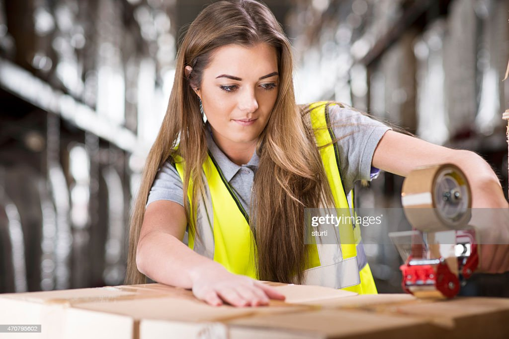 Young female warehouse worker packing boxes for shipment stock young female warehouse worker packing boxes for shipment stock photo sciox Choice Image