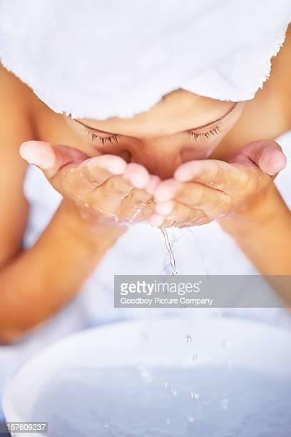 Jeune femme Se laver le visage dans un évier