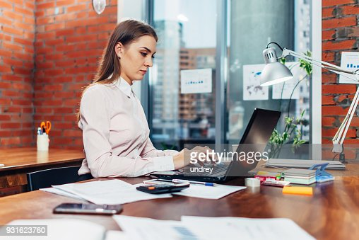 Young female wearing formal clothes working on laptop typing emails sitting at her workplace : Stock Photo