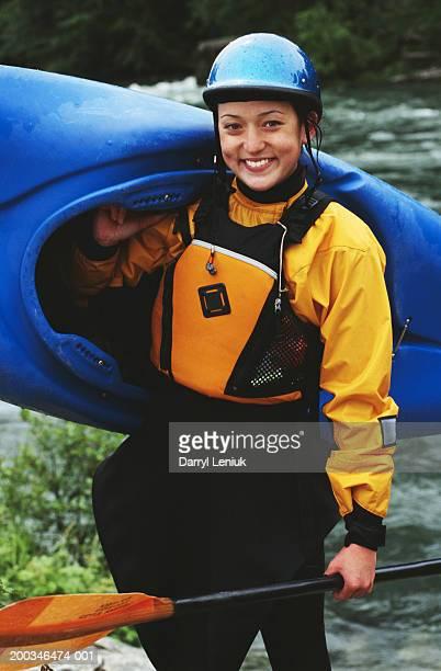 Young female white-water kayaker holding kayak, smiling, portrait